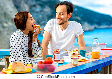 Young couple having breakfast outdoors