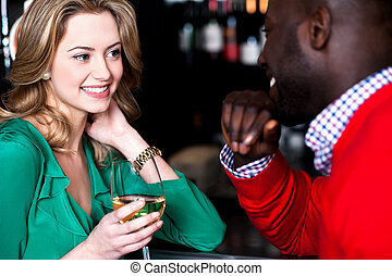 Young couple having conversation in bar