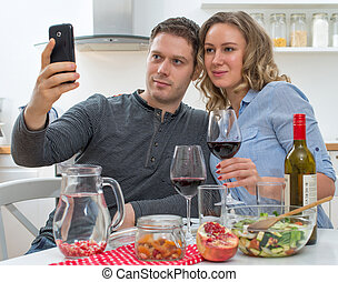 Young couple having dinner at home. Taking selfie with mobile phone.