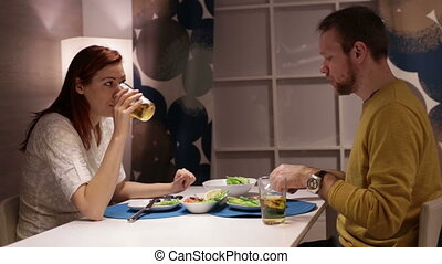 Young couple having dinner at the table.