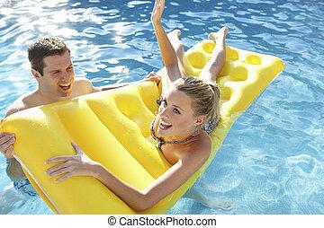 Young couple having fun in pool