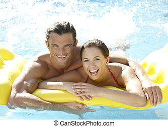 Young couple having fun in pool