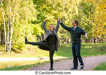 Young couple having fun in the autumn forest