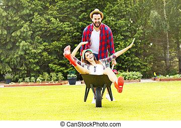 Young couple having fun in the barrow