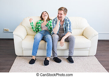 Young couple having fun laughing on sofa
