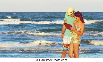 Young couple having fun on a summer day by the sea with a tablet
