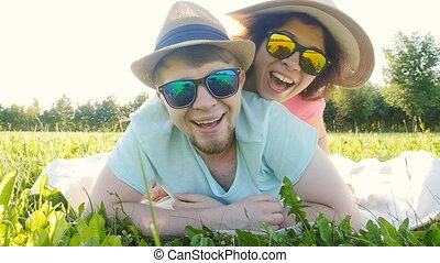 Young couple having fun on the grass in a park - Young...
