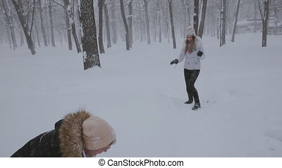 young couple having fun together in snow in winter woodland throwing snowballs