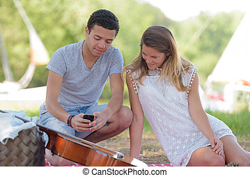 young couple having fun with guitar in the park