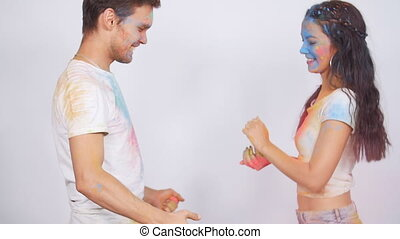 Young couple having fun with holi paints on a white...