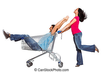 Young couple having fun with shopping cart on white...