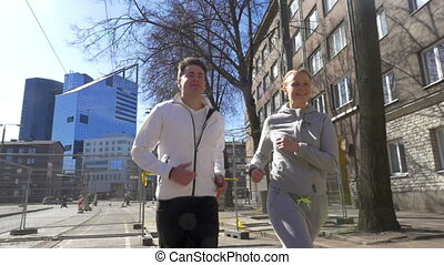 Young couple having morning run in the city