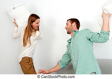 Young couple having pillow fight. - Young attractive couple...