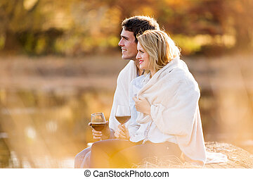 young couple having red wine outdoors