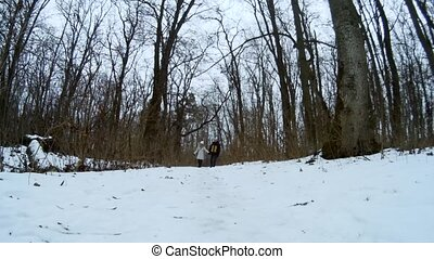 Young couple hiking in beautiful winter forest