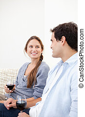 Young Couple holding a glass while looking each other