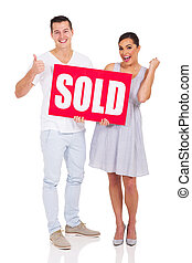 young couple holding a sold sign