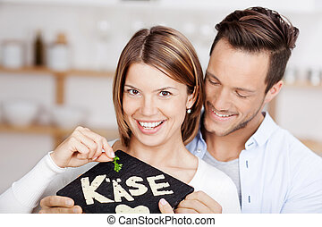 Young couple holding a stone slab with cheese