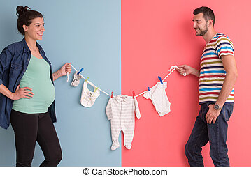 young couple holding baby bodysuits