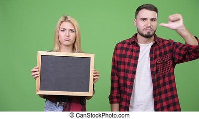 Young couple holding blackboard giving thumbs down together...
