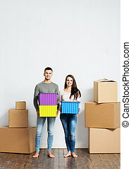 Young couple holding boxes in their new home