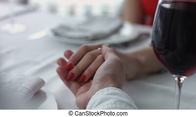 Young couple holding each other hands at the restaurant.