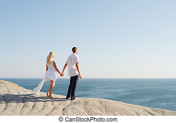 Young couple holding hands and looking at the sea