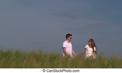 Young couple holding hands and walking through wheat field...