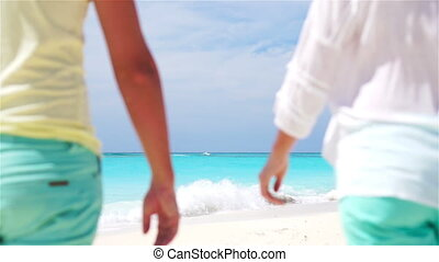 Young couple holding hands at tropical beach. Closeup SLOW MOTION