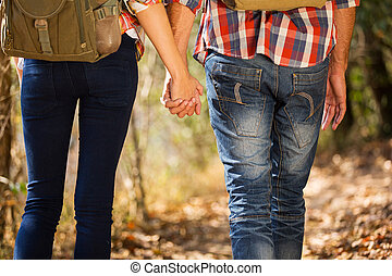 young couple holding hands hiking in mountain