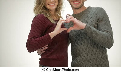 Young couple holding hands in a heart shape
