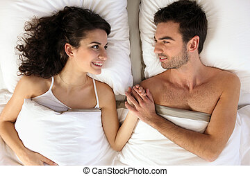 Young couple holding hands in bed