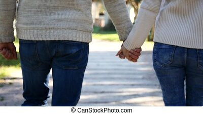 Young couple holding hands, outdoors in slow motion