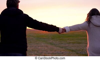 Young couple holding hands run through a wide field, having fun outdoors, slow motion