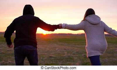 Young couple holding hands run through a wide field, having fun outdoors