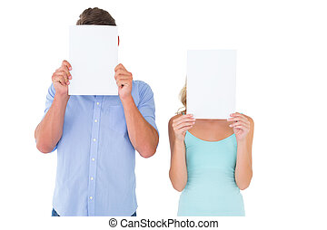 Young couple holding pages over their faces