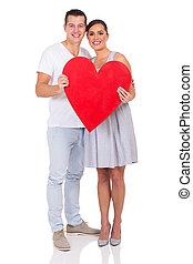 young couple holding red heart symbol