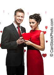 young couple holding red heart
