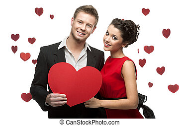 young couple holding sign in form of red heart