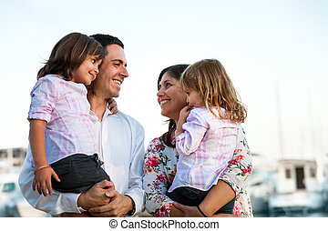 Young couple holding their kids in arms outdoors.