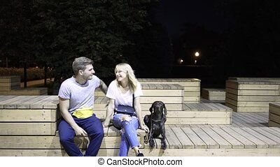 Young couple hugging and kissing. Their dog is near them. A night park