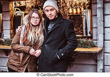 Young couple hugging and looking at the camera while standing near the counter with souvenirs at the winter Christmas Fair