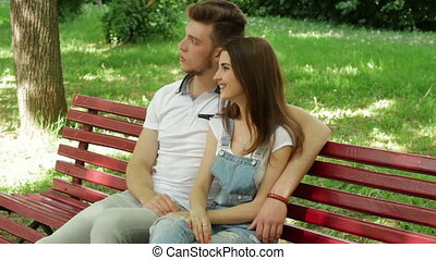 young couple hugging and talking on a bench in the Park