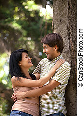 Young couple hugging. Beautiful young couple hugging and looking at each other while leaning on the tree in a park