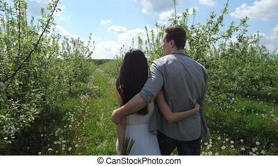 Young couple hugging during walk in apple orchard