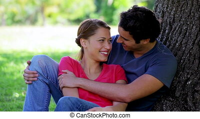 Young couple hugging each other while leaning against a tree