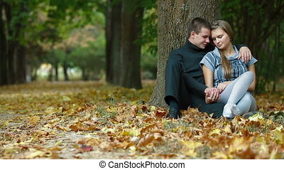 Young couple hugging on fallen leaves in autumn park