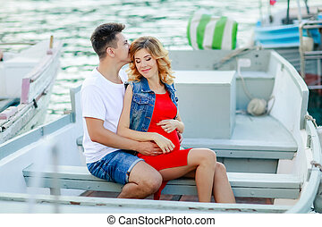 Young couple hugs and relaxing at dock near boat, on sunny summer day. Woman and man in fashionable clothes stands near luxury yacht. Luxury life concept. Couple in love travelling, honeymoon time.