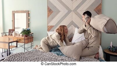 young couple husband and wife playing with pillows