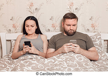 Young couple in a bed with mobile phones